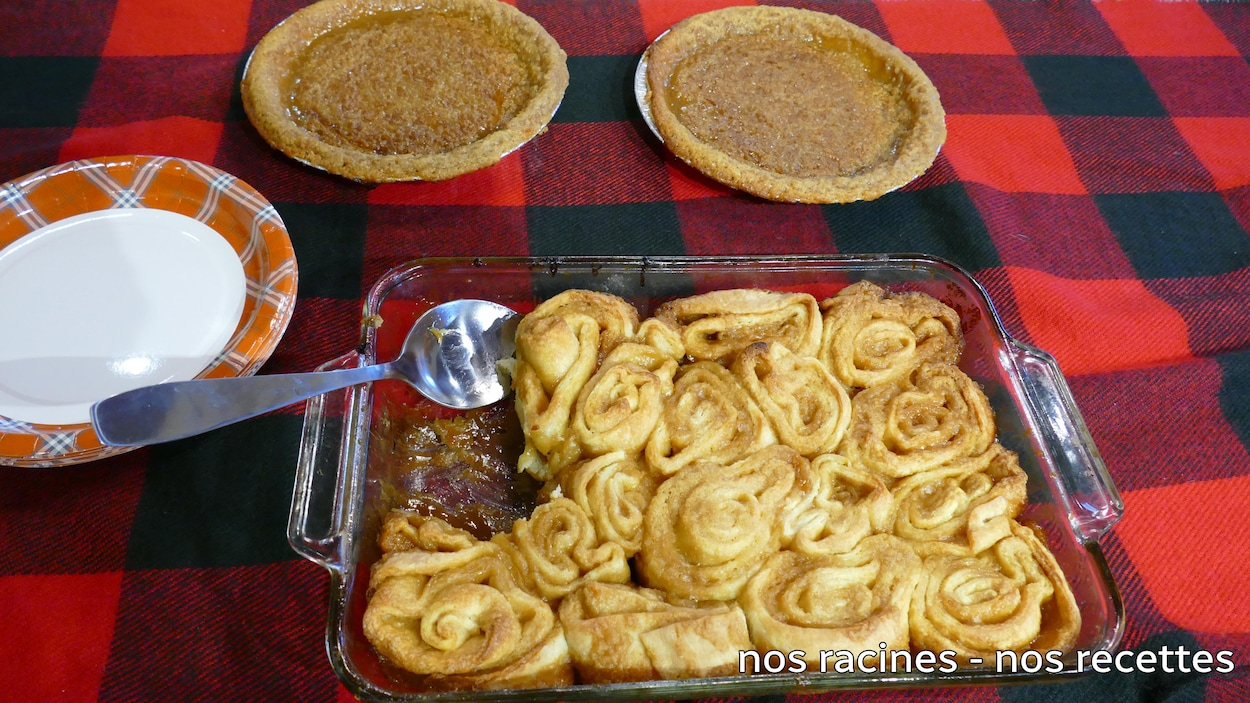 Sur une nappe carreautée rouge et noire, deux tartes au sucre et un gros plat de brioches.