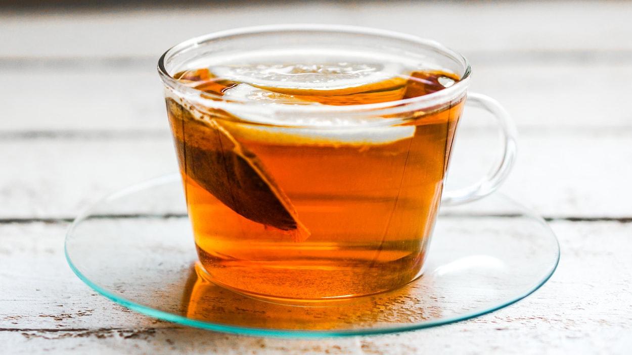 Un sachet de thé infuse dans une tasse transparente.
