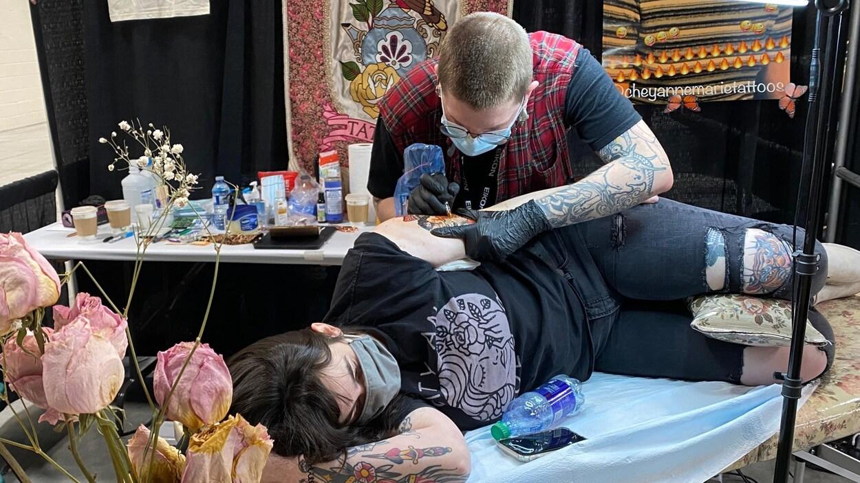 Un homme tatoue le bras d'une jeune femme.