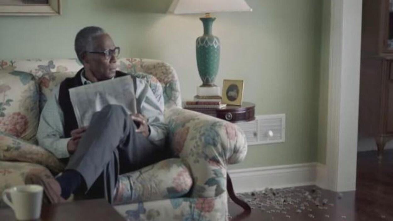 Un homme lisant un journal et regardant de l'argent tombé par une bouche d'aération.