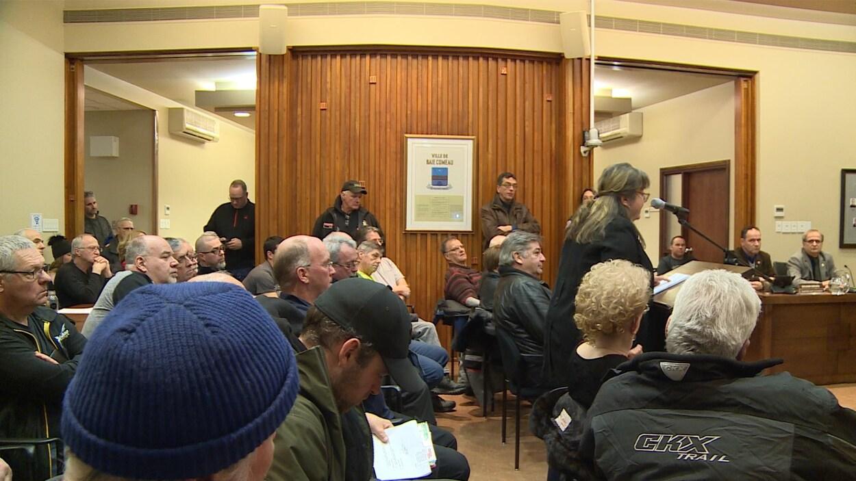 La salle était bondée et des gens ont dû s'asseoir dans le couloir.