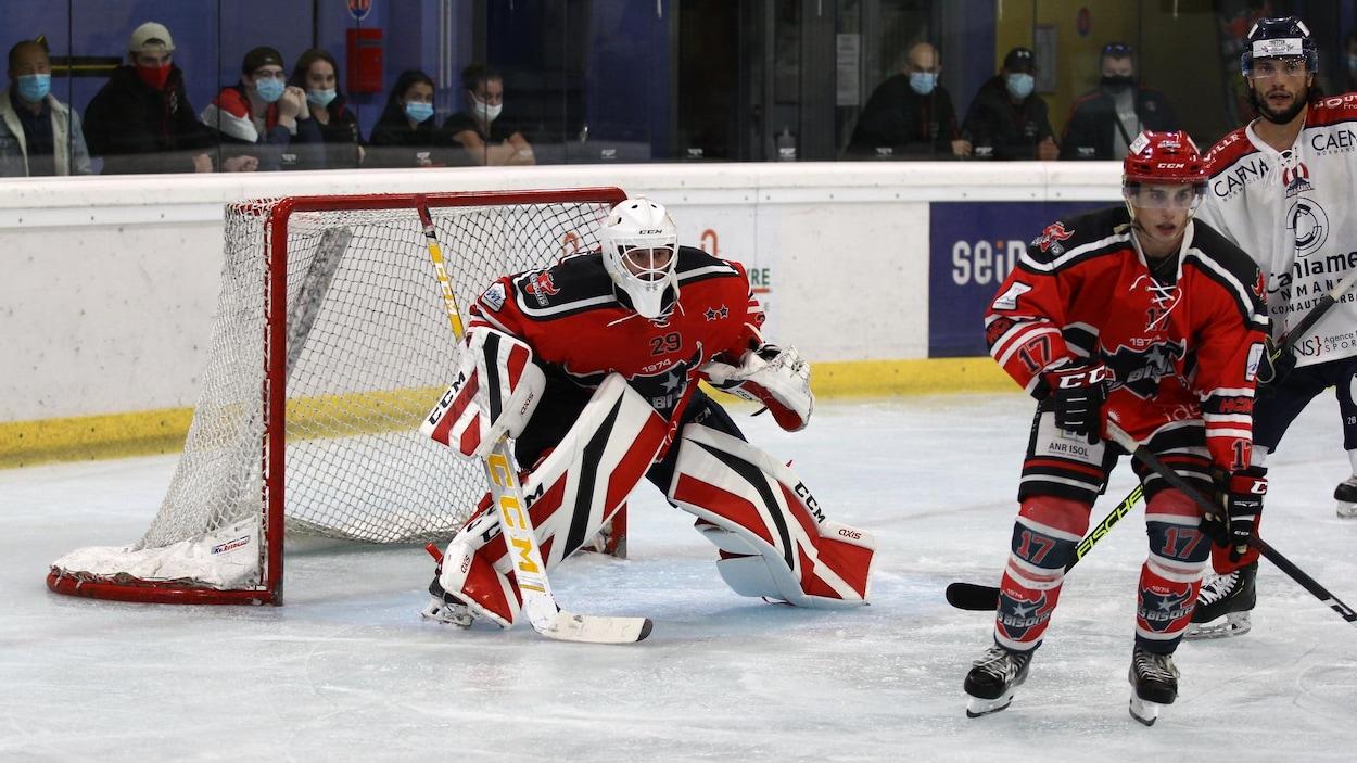 Taylor Dupuis garde les buts devant son filet alors que deux autres joueurs se trouvent à proximité.