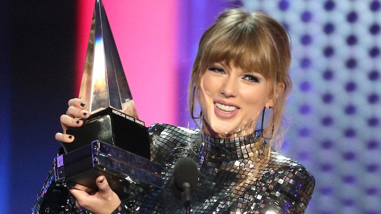 Taylor Swift brandit un trophée dans ses mains devant un micro sur scène