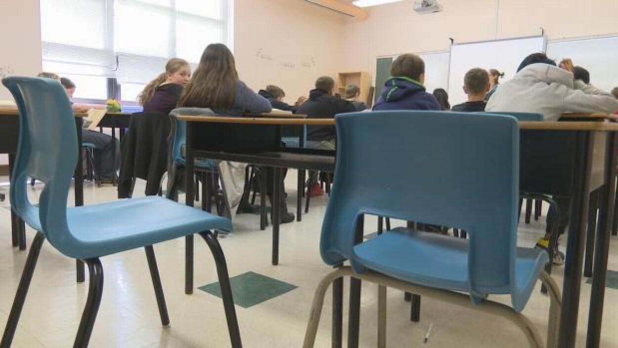 Une salle de classe et des élèves, assis, de dos.
