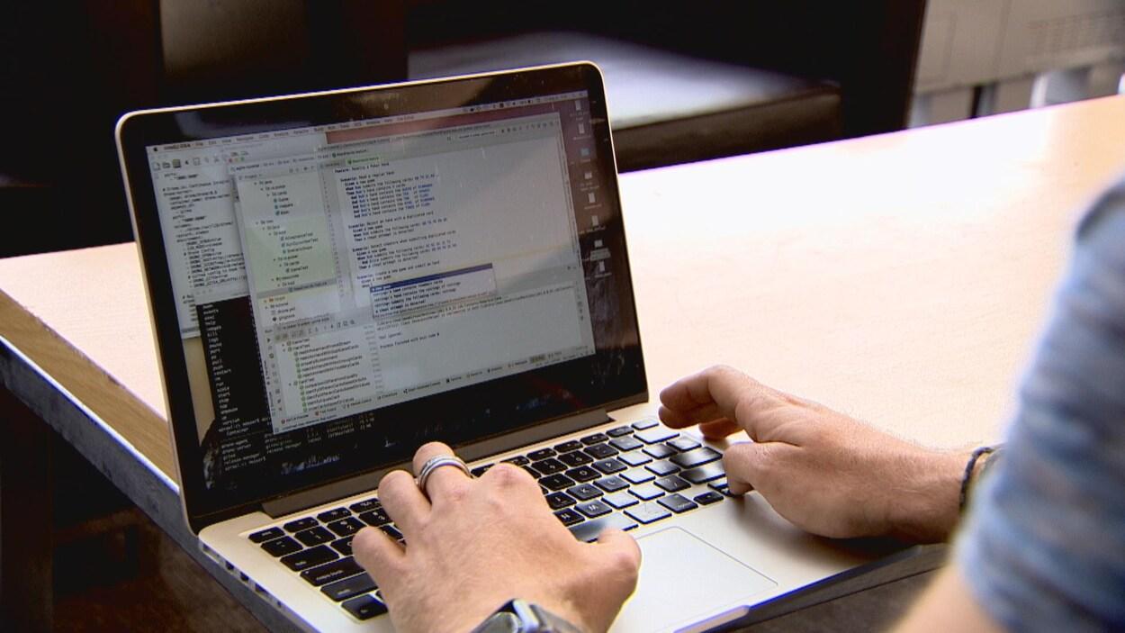 Un ordinateur portable avec des insciptions codées. On voit les mains d'une personne sur le clavier.