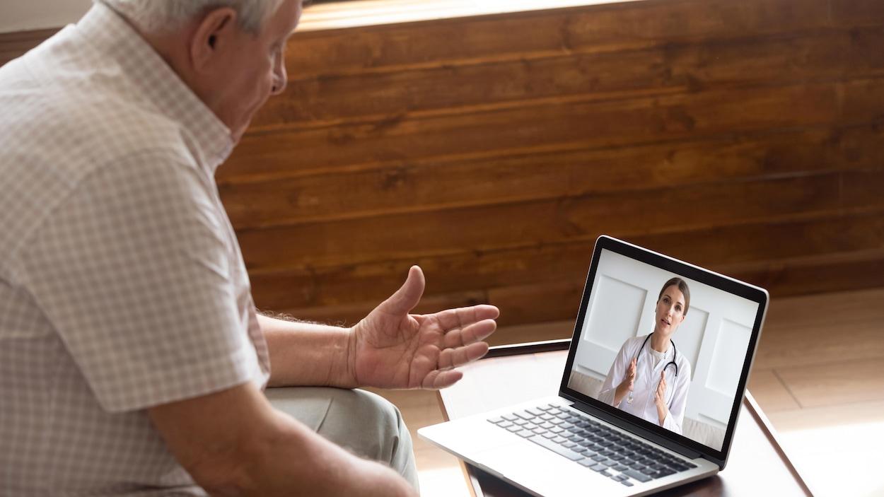 Une homme âgé parle à une spécialiste de la santé lors d'une consultation en ligne.
