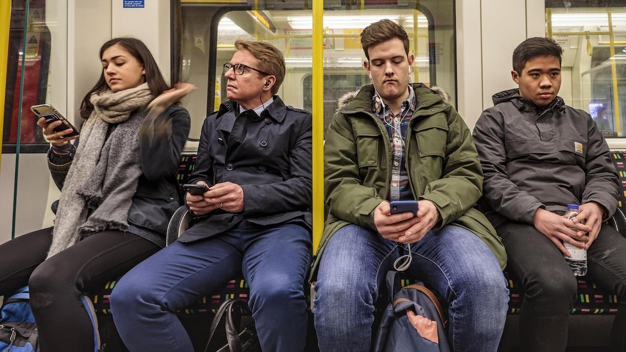 Quatre passagers assis côte à côte sur une banquette de métro. Trois d'entre eux tiennent leur téléphone entre leurs mains.