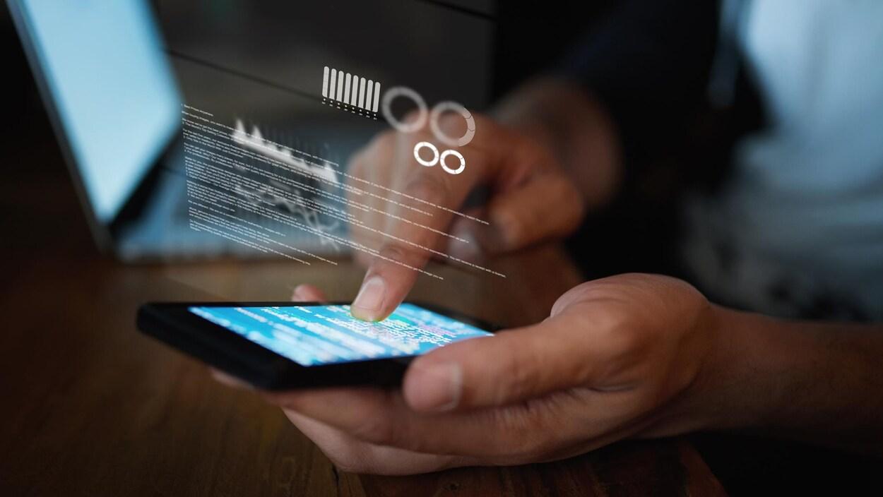 Un gros plan sur les mains d'une personne en train d'utiliser un téléphone cellulaire.