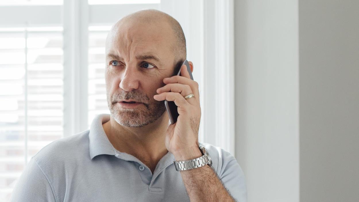 Un homme debout près d'une fenêtre parle au téléphone l'air inquiet.