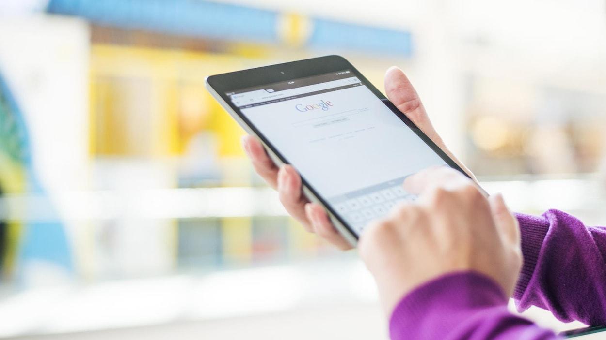Une personne écrit sur son téléphone portable devant un magasin.
