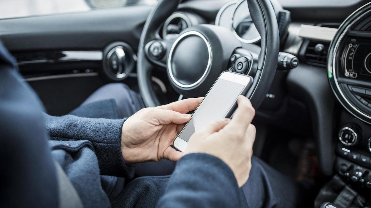 Un homme assis dans une voiture utilise son téléphone cellulaire.