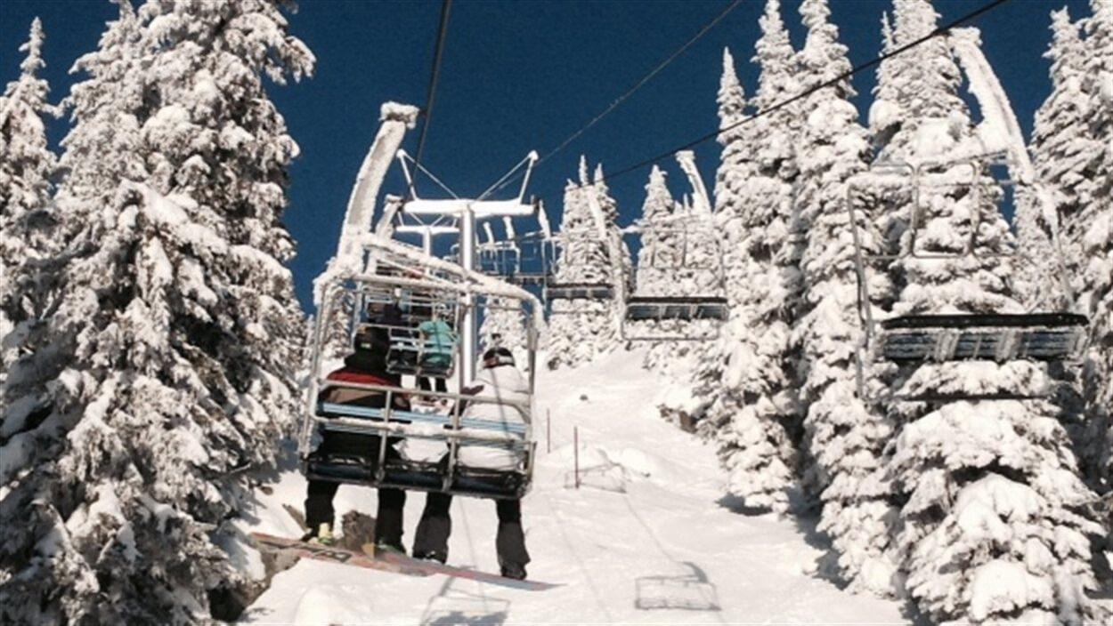 Deux planchistes sont assis dans un siège qui remonte une pente enneigée bordée d'arbres couverts de neige.