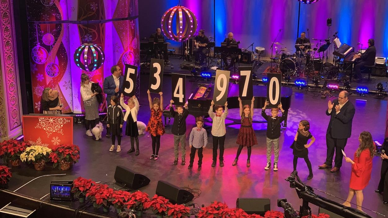 Des enfants tiennent des chiffres qui forment le nombre 534 970$.