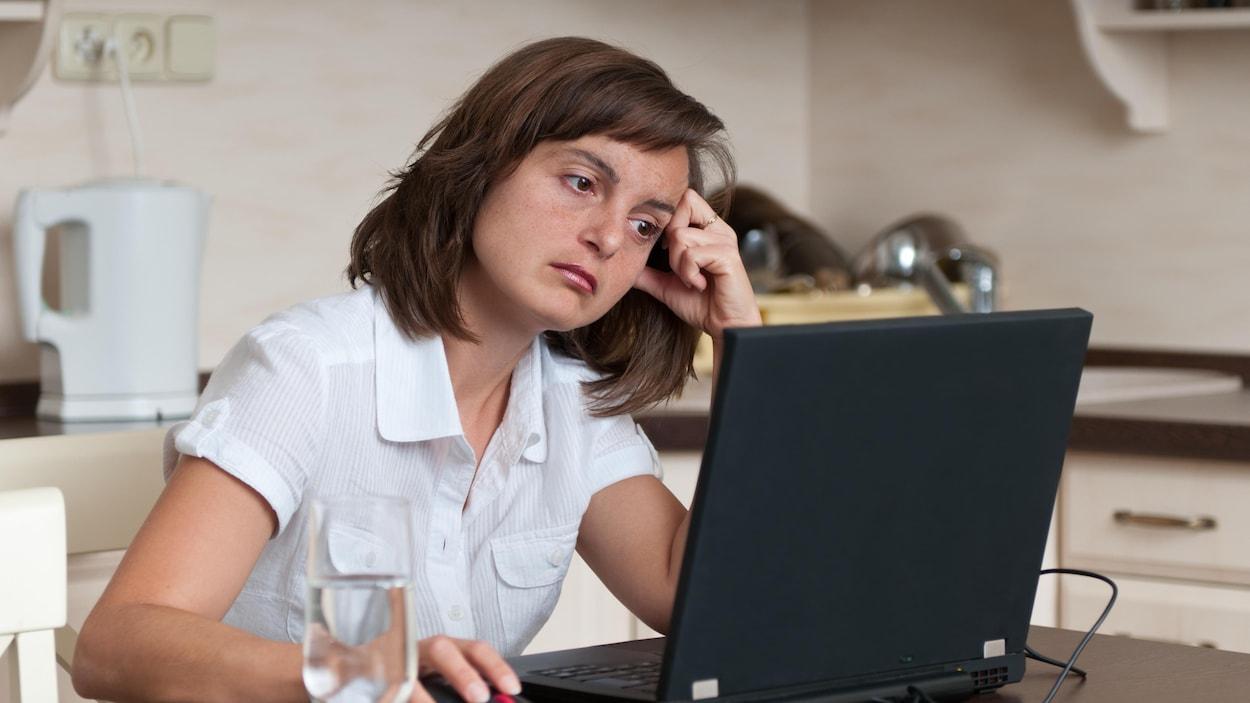 Une femme assise dans sa cuisine devant son écran d'ordinateur.