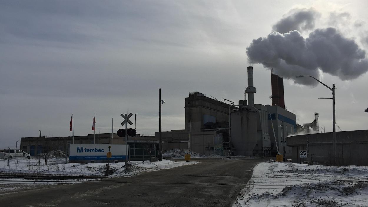 L'usine vue en hiver. Un nuage de fumée s'échappe de la cheminée.