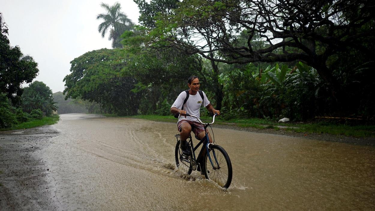 Un homme roule en vélo sur une voie inondée.