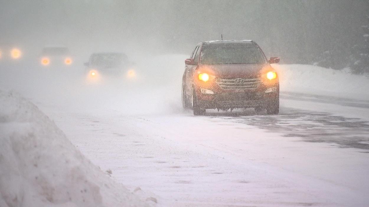 Des véhicules circulent sous la neige. La visibilité est réduite.