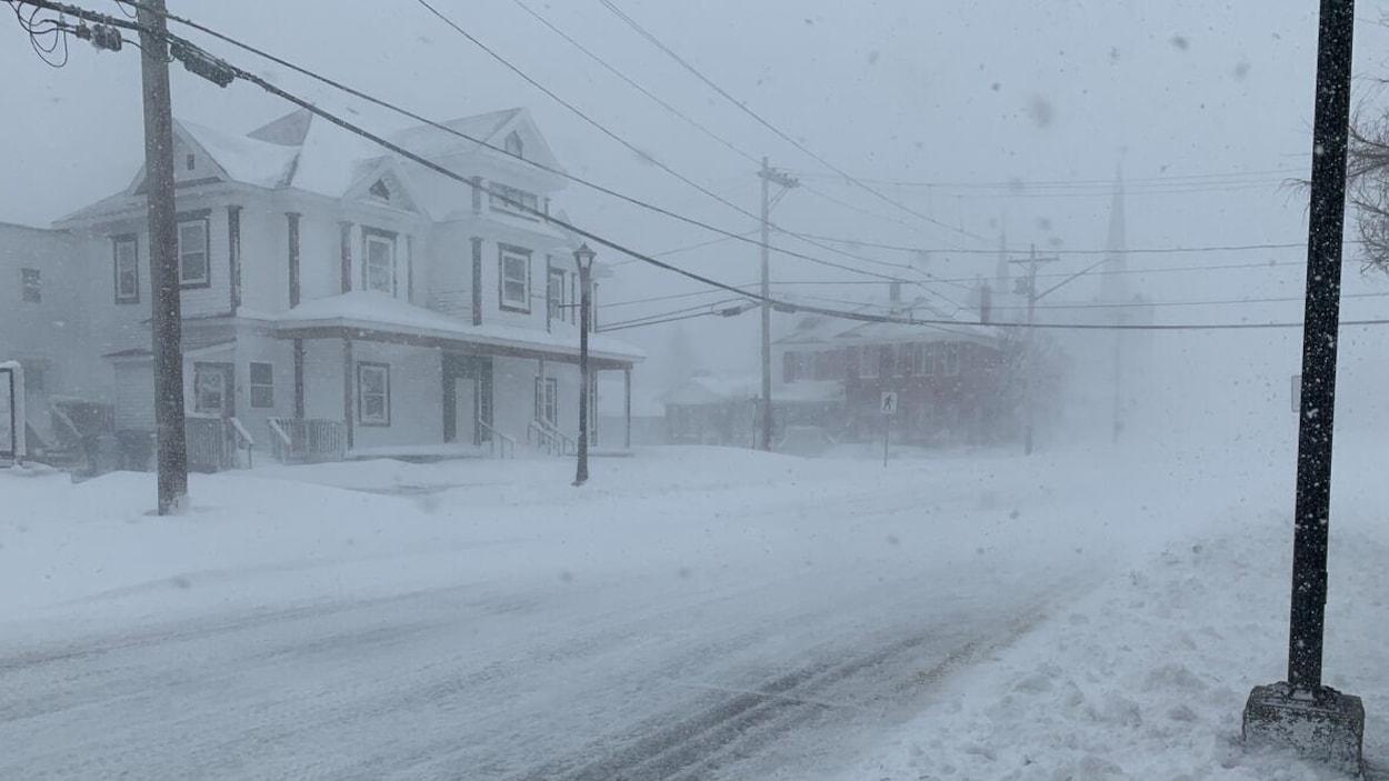 La neige tombe sur une rue déjà enneigée pendant une tempête.