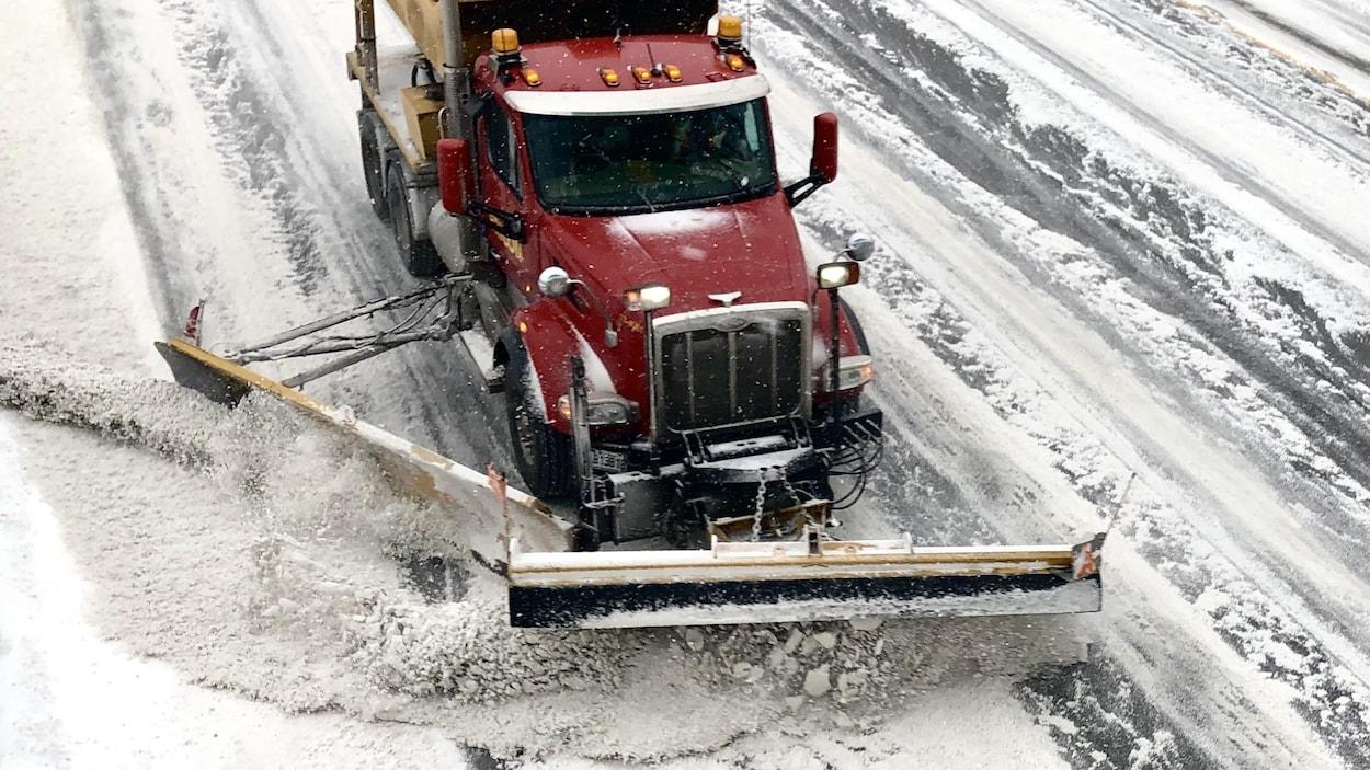 Une déneigeuse pousse de la neige sur une rue enneigée.