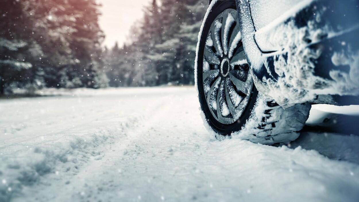 Des pneus d'auto sur une route enneigée.