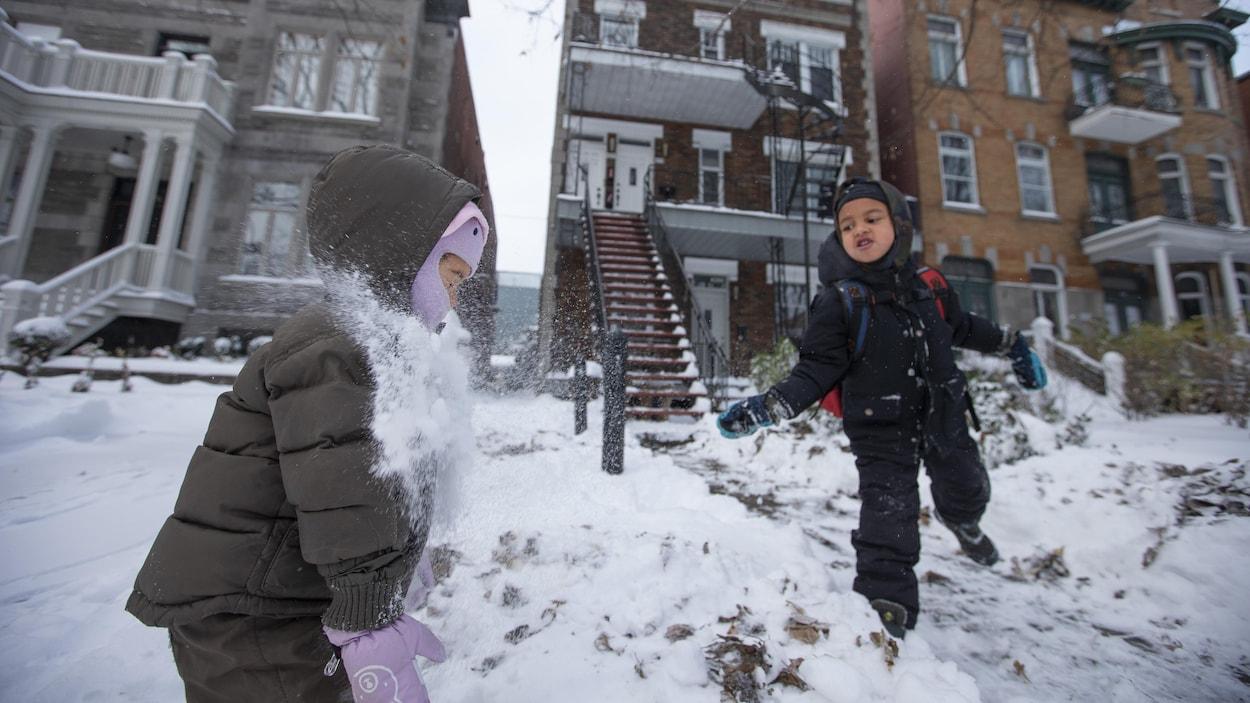 Deux enfants s'amusent dans la neige.