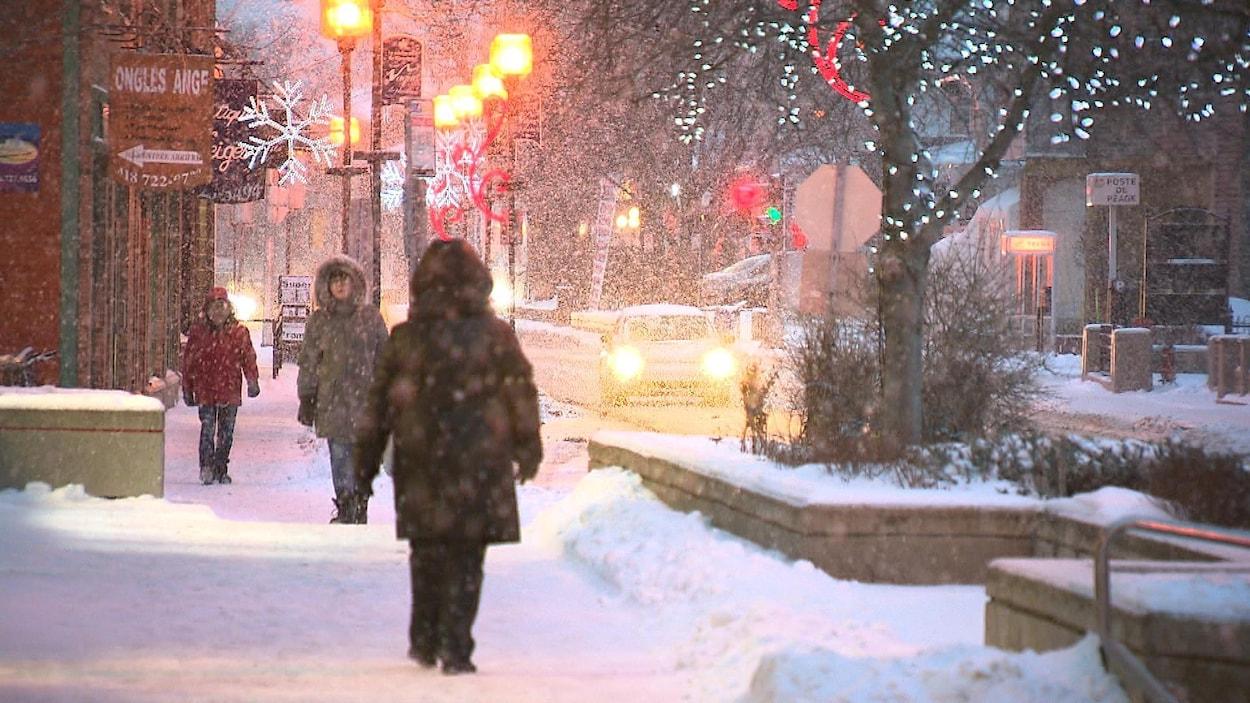 Des piétons marchent sous la neige au centre-ville de Rimouski.