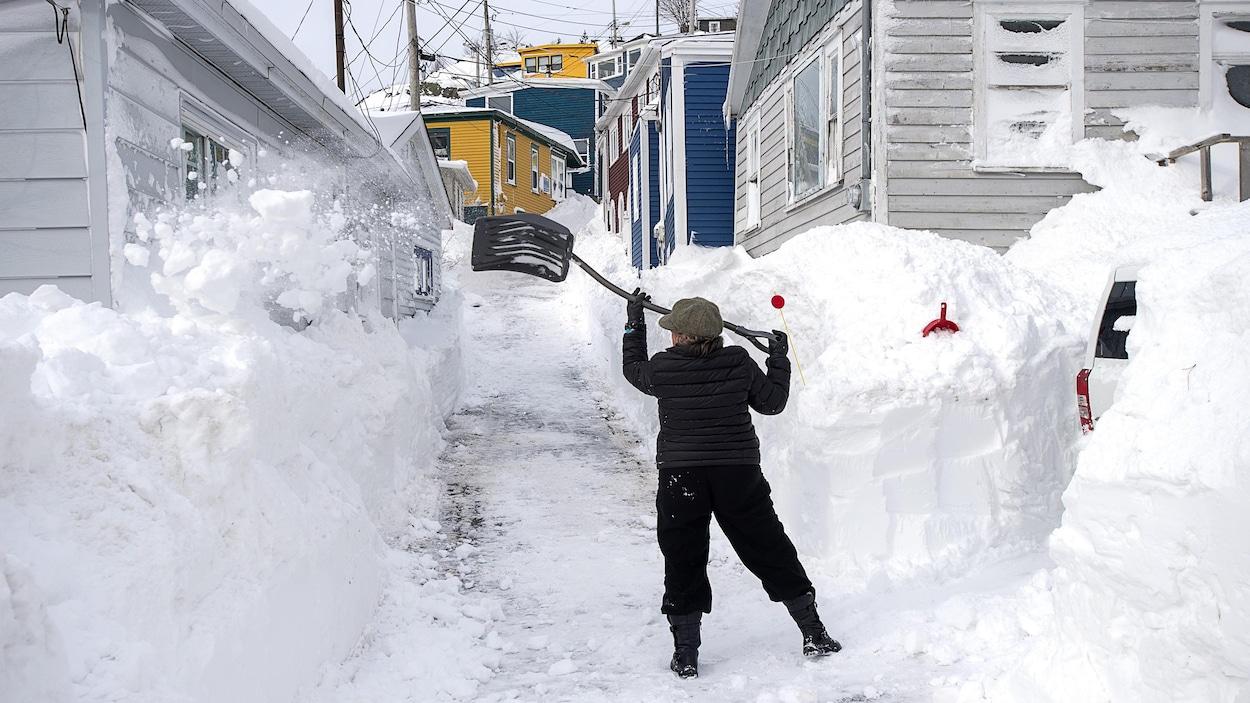 Une femme tente d'enlever la neige de son entrée de maison.