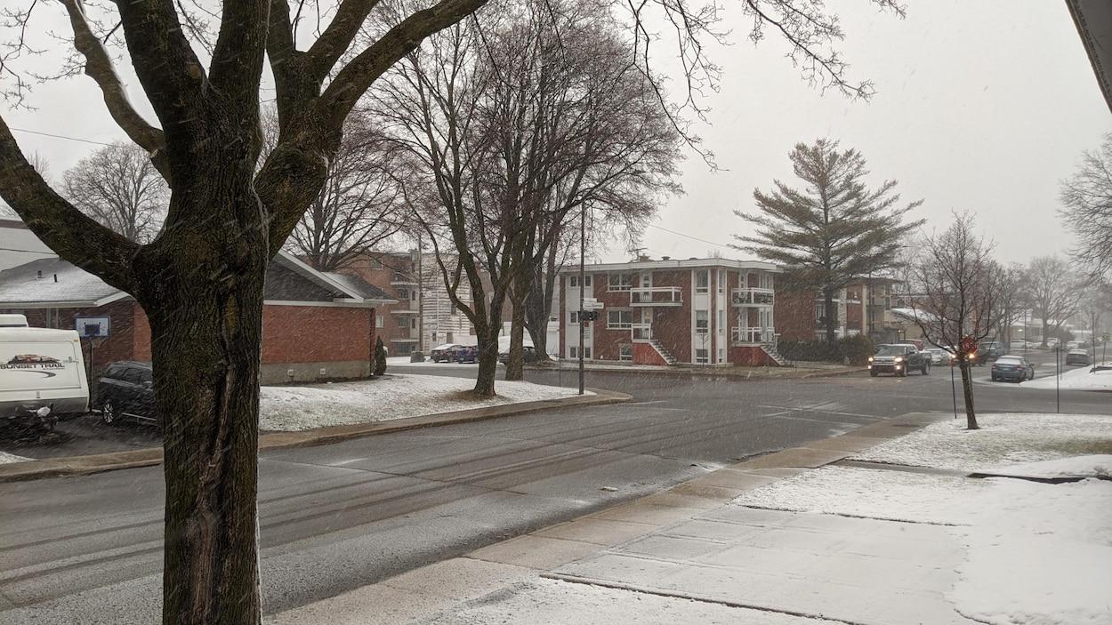 Des flocons et de la neige sur le sol au printemps dans un quartier résidentiel