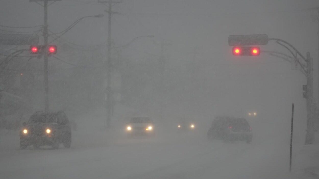 Des véhicules circulent dans les rues de Rimouski où la neige réduit la visibilité.