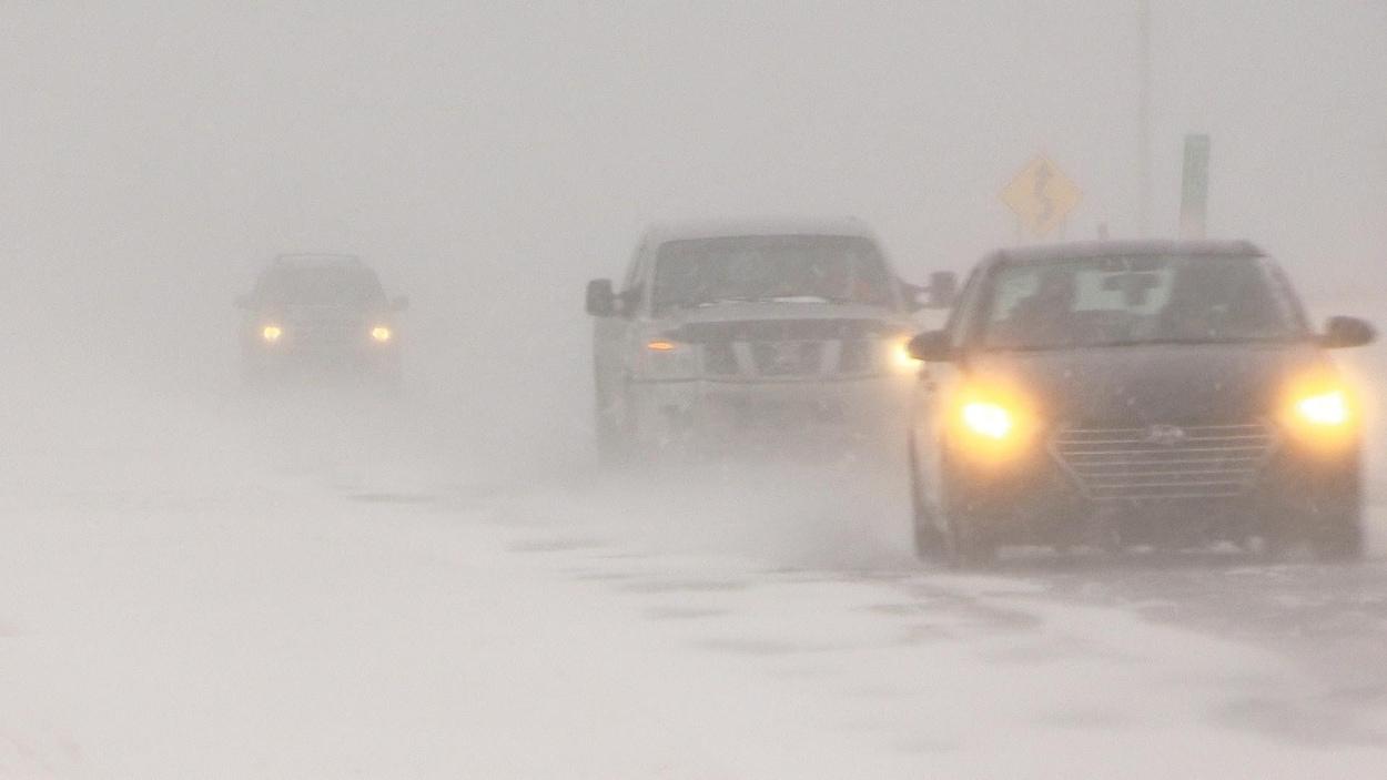 Des bourrasques soufflent de la neige devant les voitures.