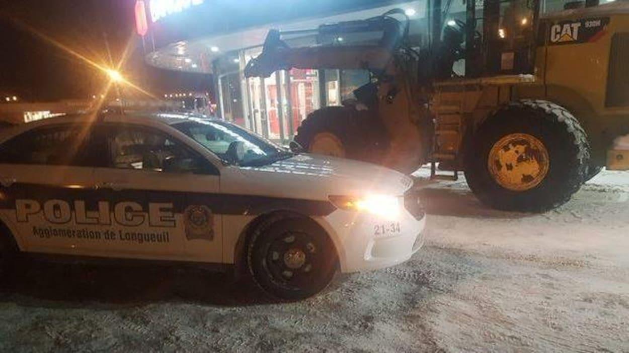 Une voiture du Service de police de l'agglomération de Longueuil devant une excavatrice