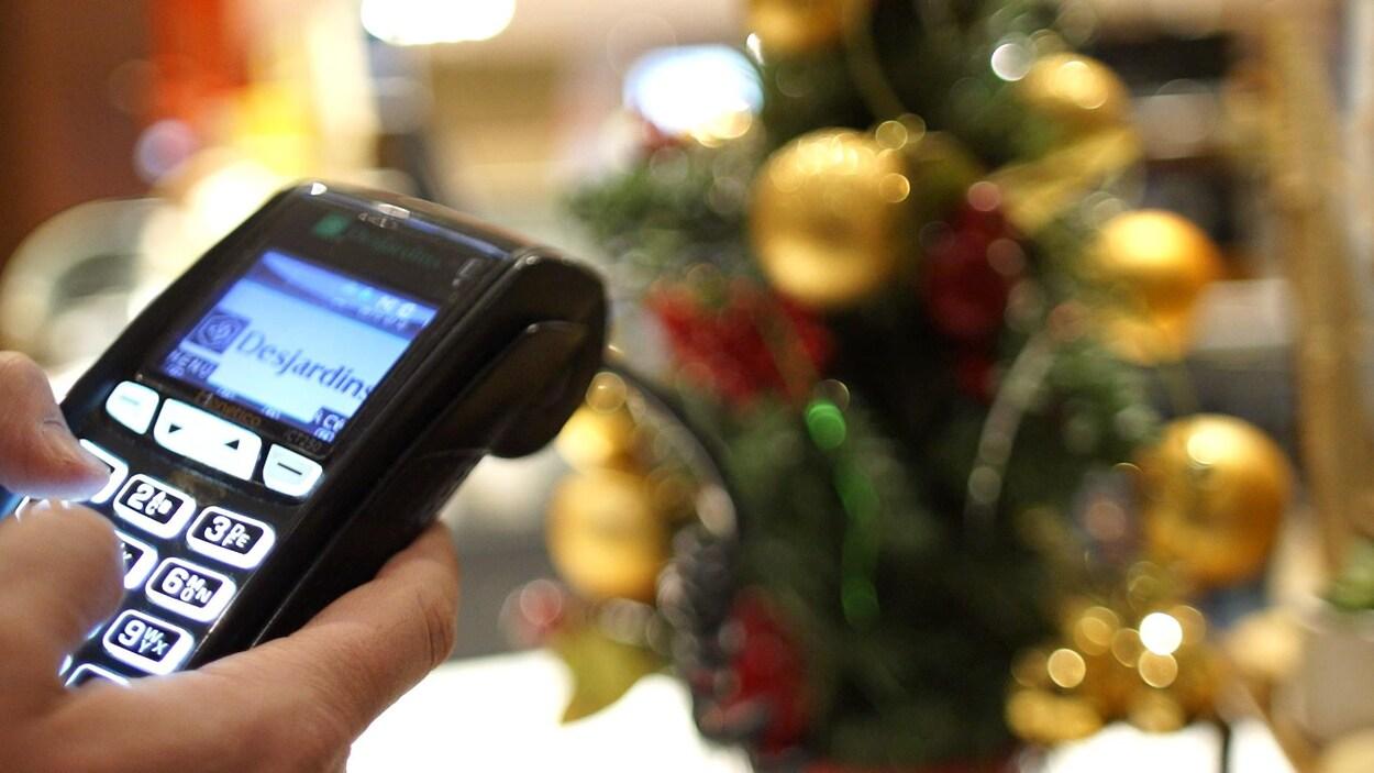 Un terminal de paiement devant un arbre de Noël