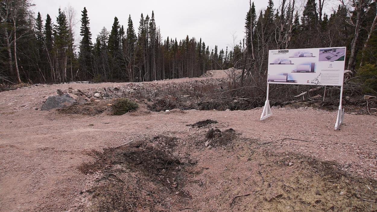 Une affiche du projet Mason Graphite devant un terrain vague.