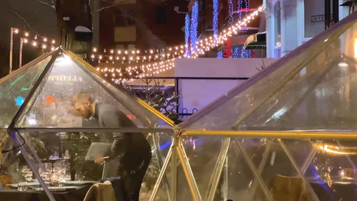 Un serveur penché au-dessus d'une table dans un dôme transparent