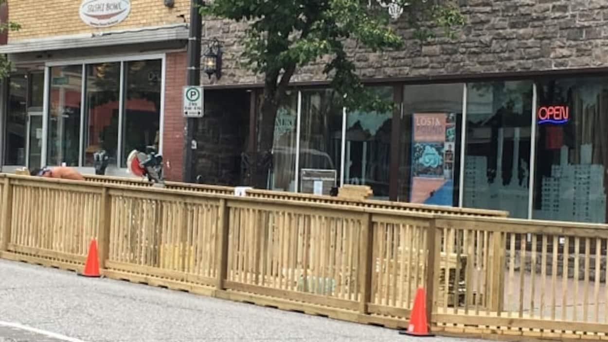 Une terrasse et un trottoir en bois devant un restaurant.