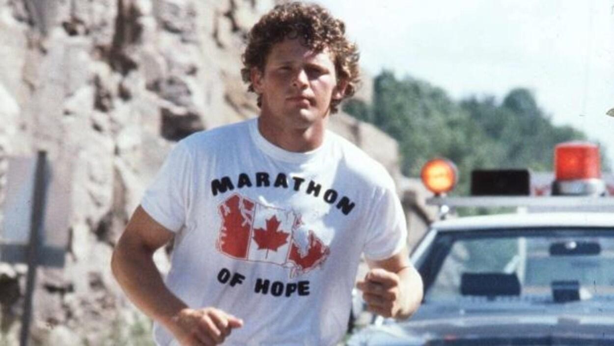 Terry Fox court avec un chandail inscrit marathon de l'espoir en anglais (marathon of hope).