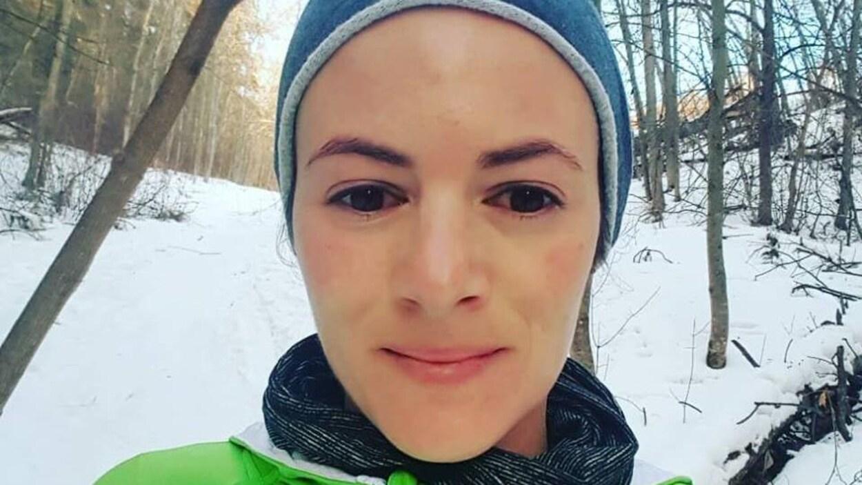 Une femme, qui porte un bonnet, se tient debout au milieu des bois.