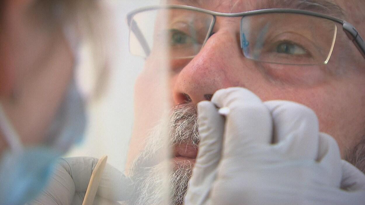 Une infirmière insère un écouvillon dans le nez d'un homme.