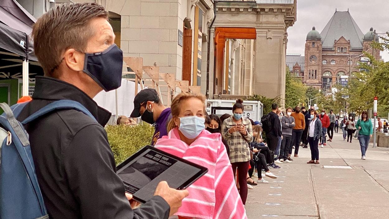 Des gens attendent en ligne pour subir un test de dépistage à Toronto.