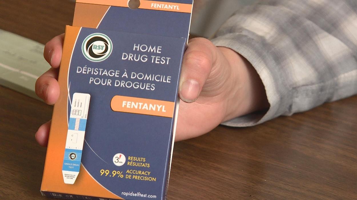 Une main tient la boite où il est écrit « dépistage à domicile pour drogues ».