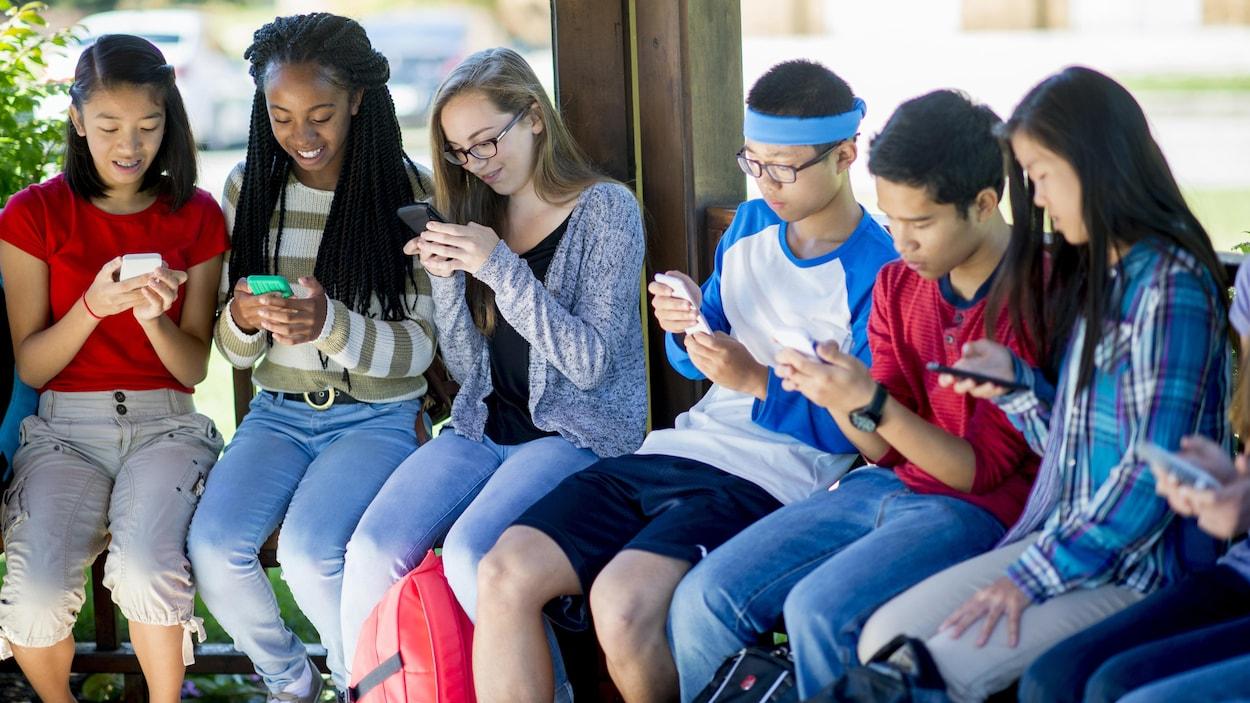 Un groupe de jeunes multiethniques assis sur un banc en train d'utiliser leur téléphone intelligent.