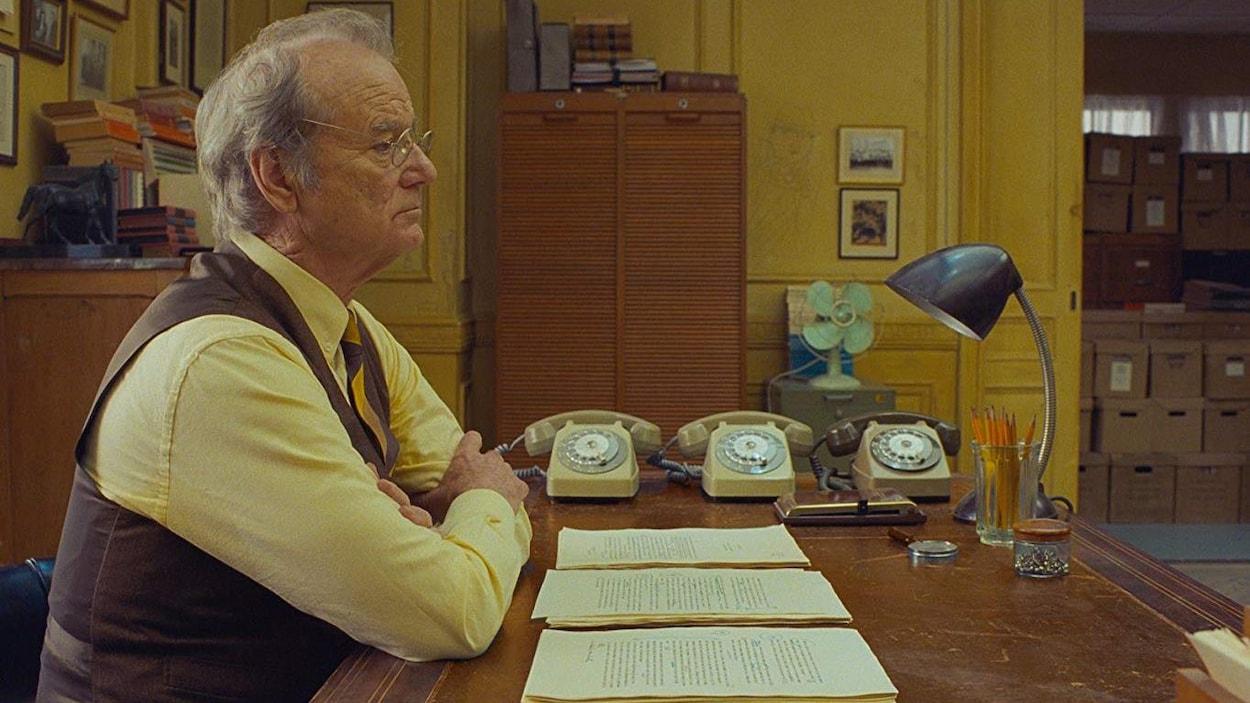 L'homme est assis à son bureau avec trois téléphones.
