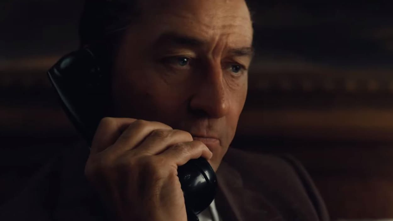 Un homme vêtu d'un veston brun tient un combiné de téléphone dans sa main.
