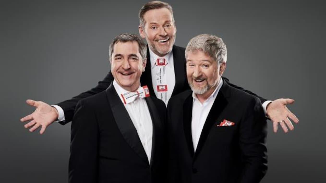 Trois hommes en habits noirs et chemises blanches sourient à la caméra.
