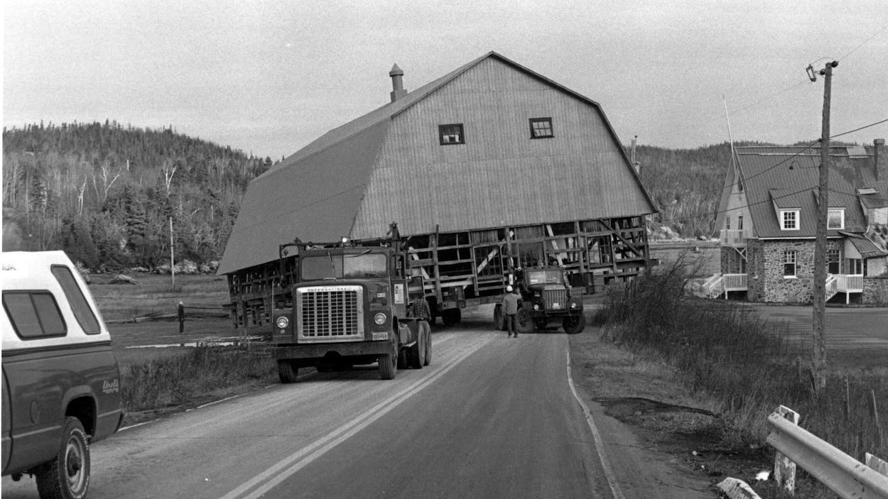 Photo d'archives en noir et blanc. Deux camions tirent une grange sur une route.