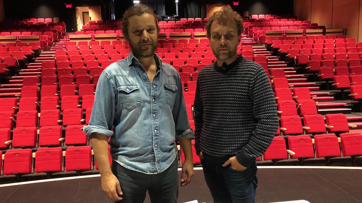 Deux hommes debout dans une salle de théâtre vide.