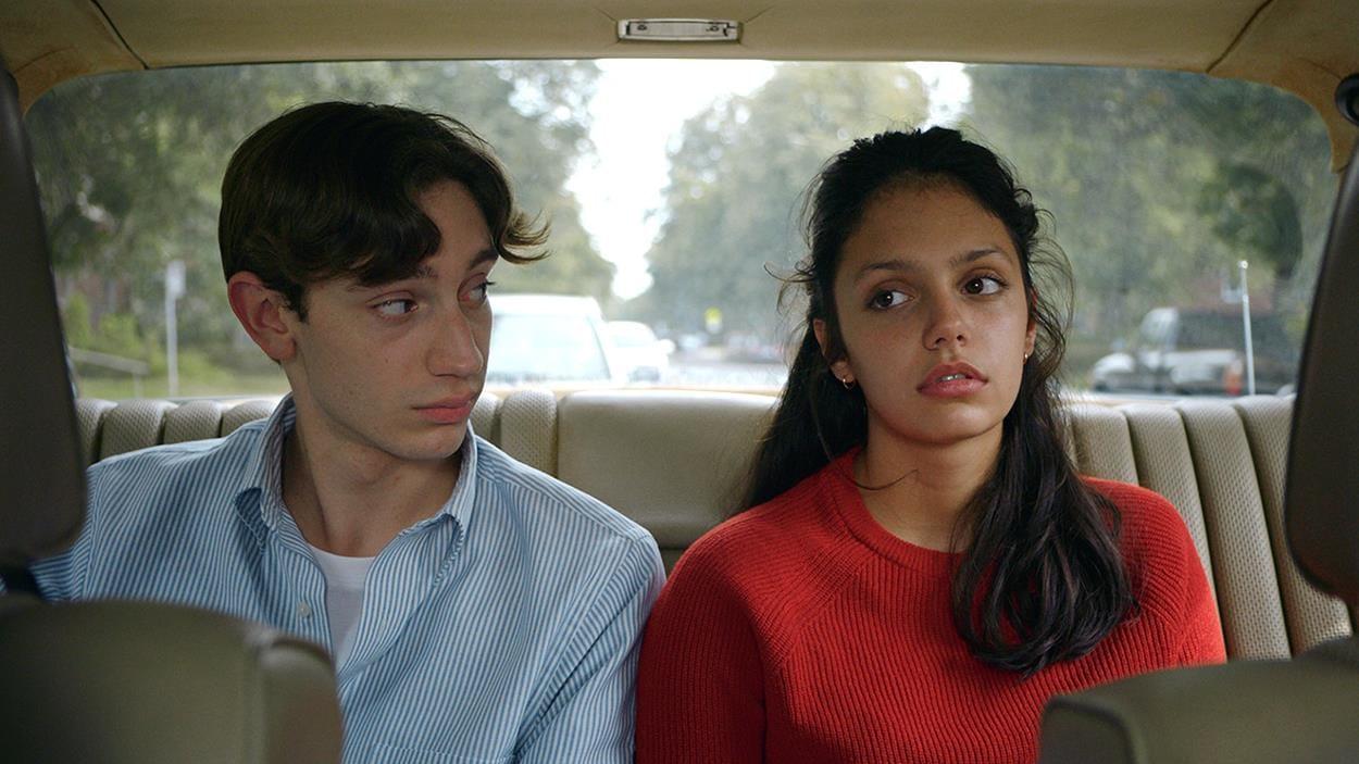 Un jeune homme et une jeune femme sont assis sur le siège arrière d'une voiture.