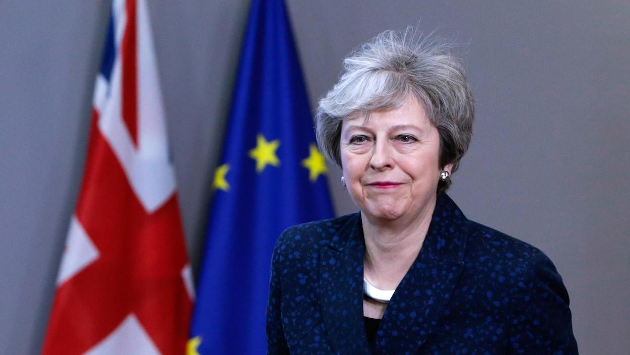 Une femme regarde devant elle alors qu'elle passe devant un drapeau britannique et un drapeau européen.