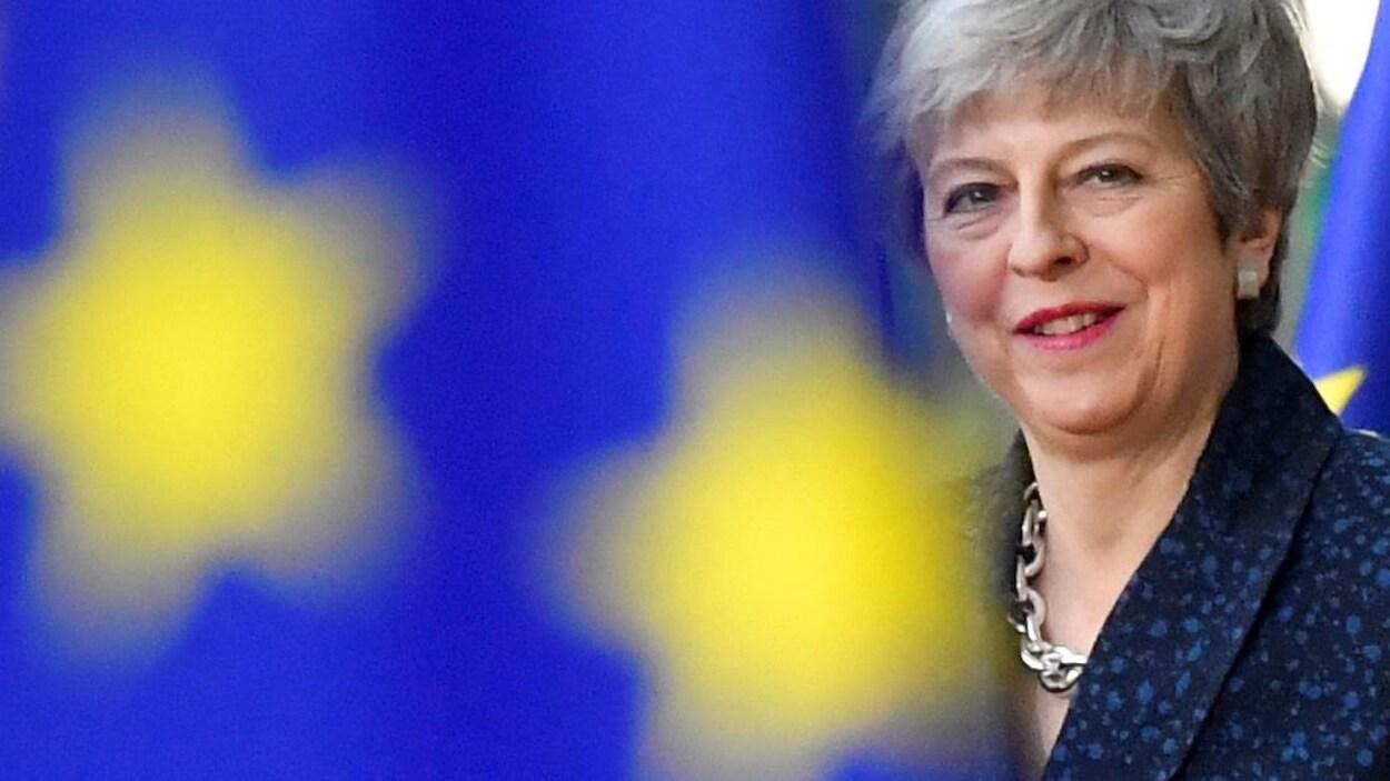 Theresa May entre deux drapeaux européens.