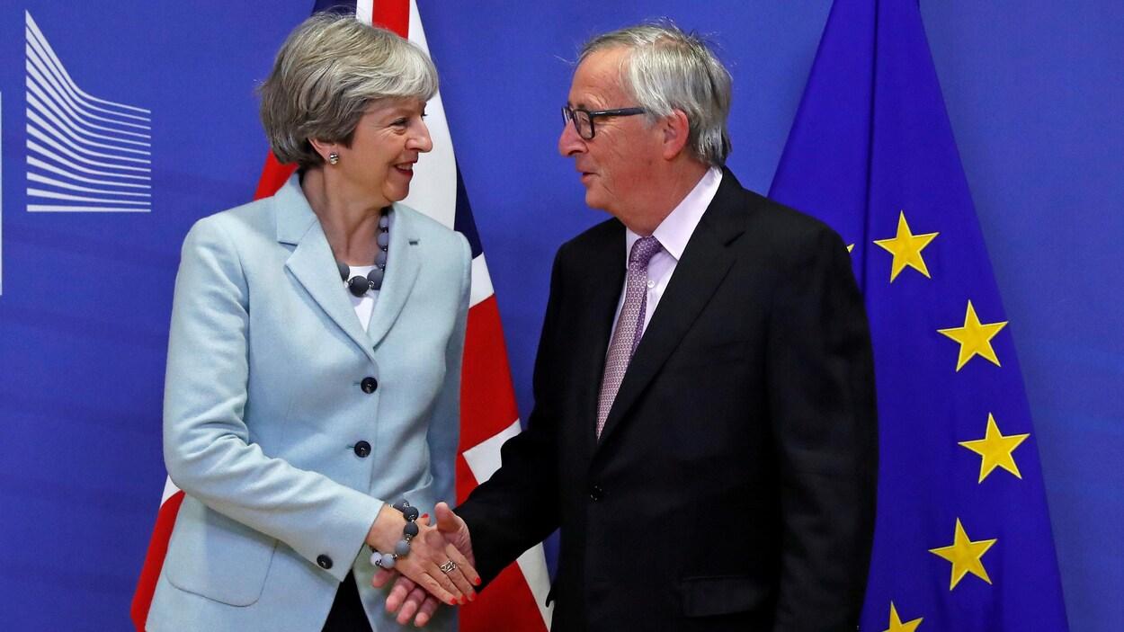 Theresa May serre la main de Jean Claude Juncker sur fond de drapeaux britannique et européen